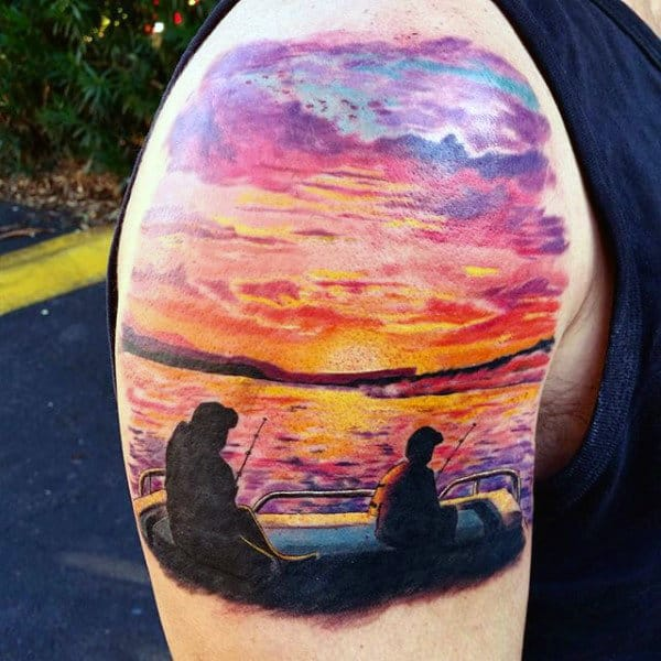 Man With Upper Arm Tattoo Of Lake Fishing At Sunset