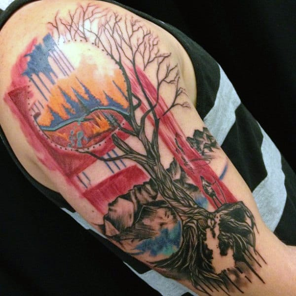 Man With Upper Arm Tattoo Of Man Standing Next To Surreal Tree Of Life