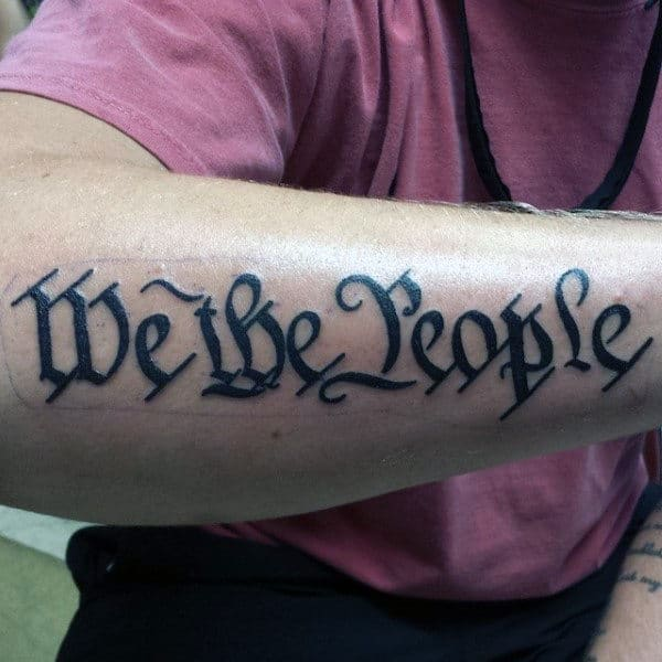 Man With We The People Black Ink Forearm Tattoo