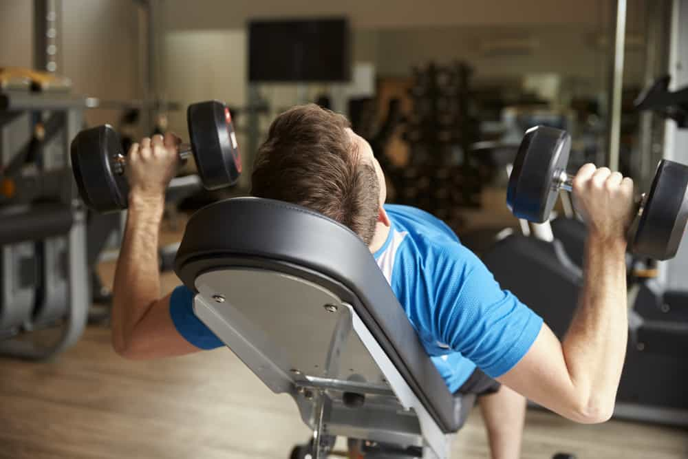 man incline dumbbell bench press works out in gym