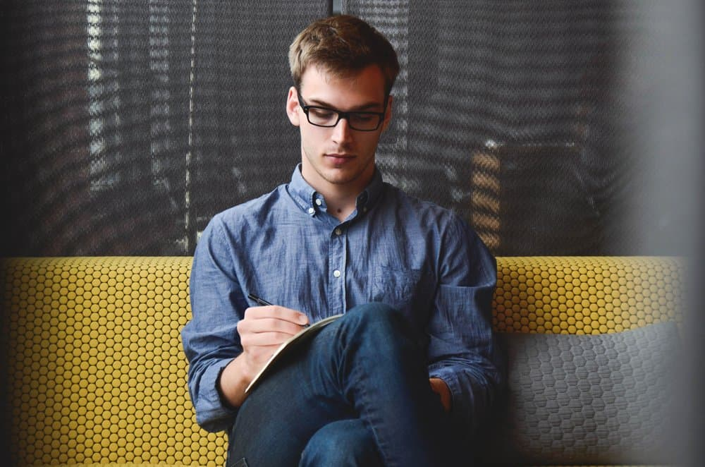 man sits on a couch writing in a notebook, wearing denim pants and a button-up denim shirt