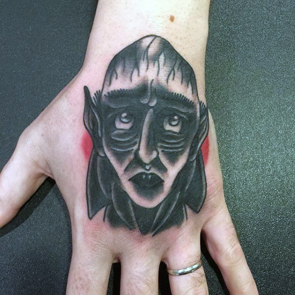Manly Old School Black And Red Vampire Tattoo On Mans Hand
