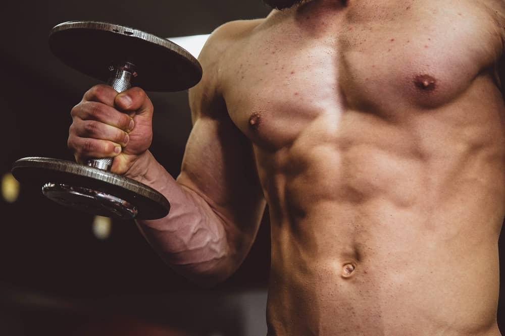 closeup shot of a man's abdominal muscles with a dumbbell clenched in one hand