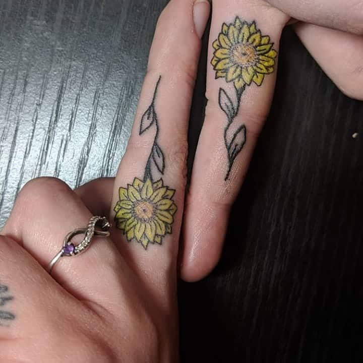 Inside middle fingers matching tiny color yellow daisies tattoos