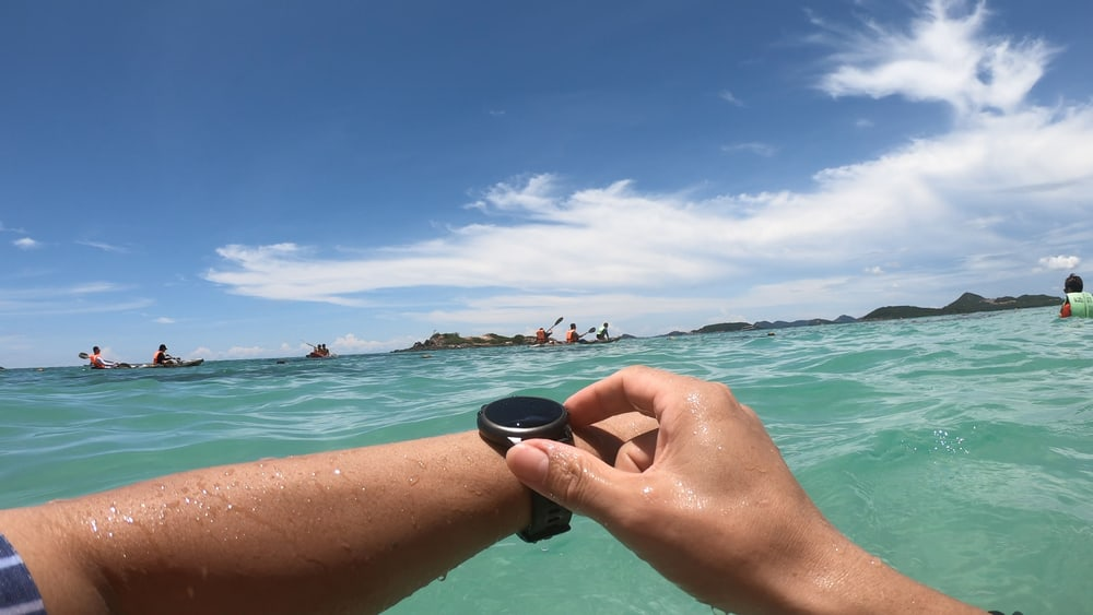 men setting wrist watch before diving into sea