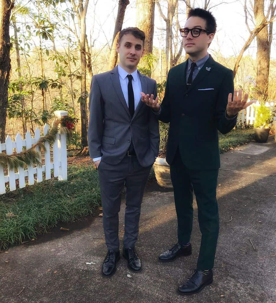 Two men outdoors wearing slim-fitting mod suits with thin neck ties