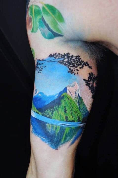 Mens Inner Biceps Blue Sunny Day Hills And Lake Tattoo