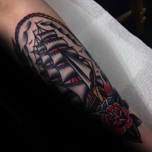 Mens Leg Tattoo Design With Traditional Sailing Ship And Red Rose Flower Design