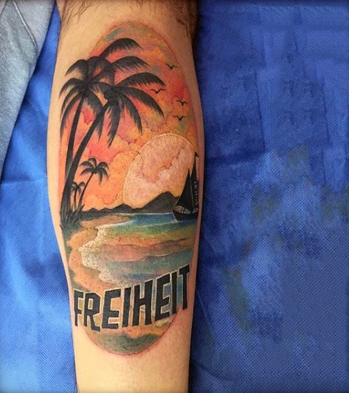 Mens Leg Tattoo Of Ship At Sunset With The Word Freiheit Traditional Style