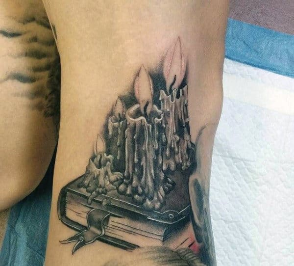 Mens Legs Burning Wax Candles Over Book Tattoo