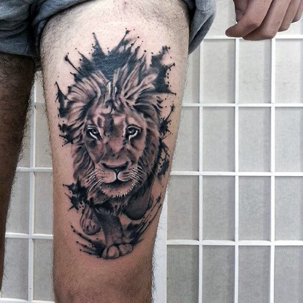 Lion leg tattoo featuring a watercolor running lion design on a man's thigh