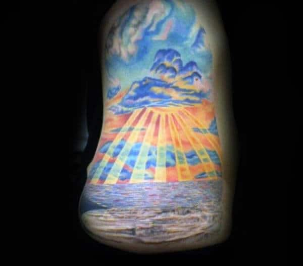 Mens Upperarm Tattoo Of Ocean Sunset With Sunrays In Color