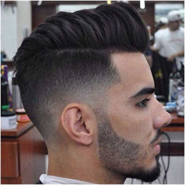 A haircut with extended hair on top and mid fade sides and back with faded hair connecting to the beard