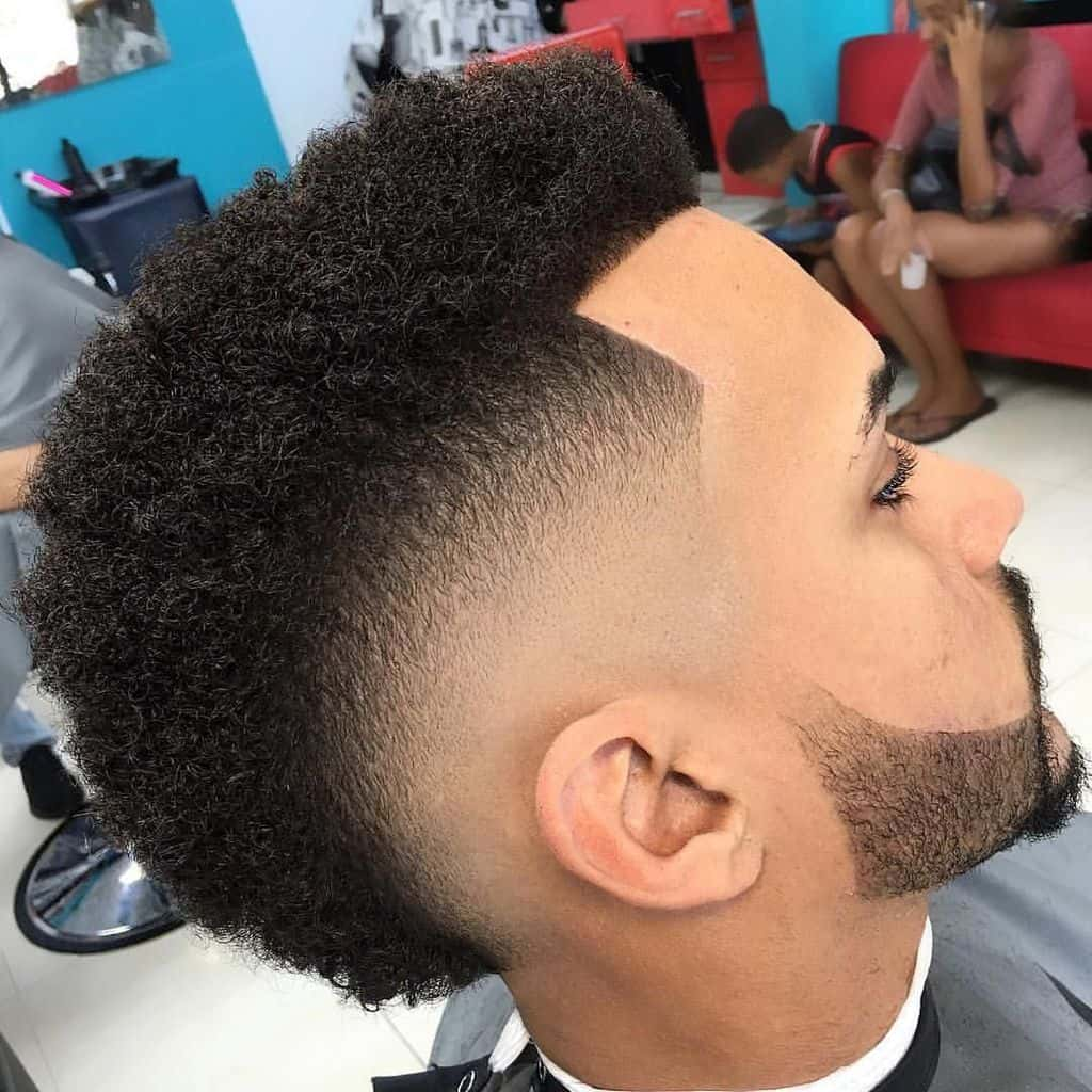 A fohawk haircut combined with a mid-fade cut and beard