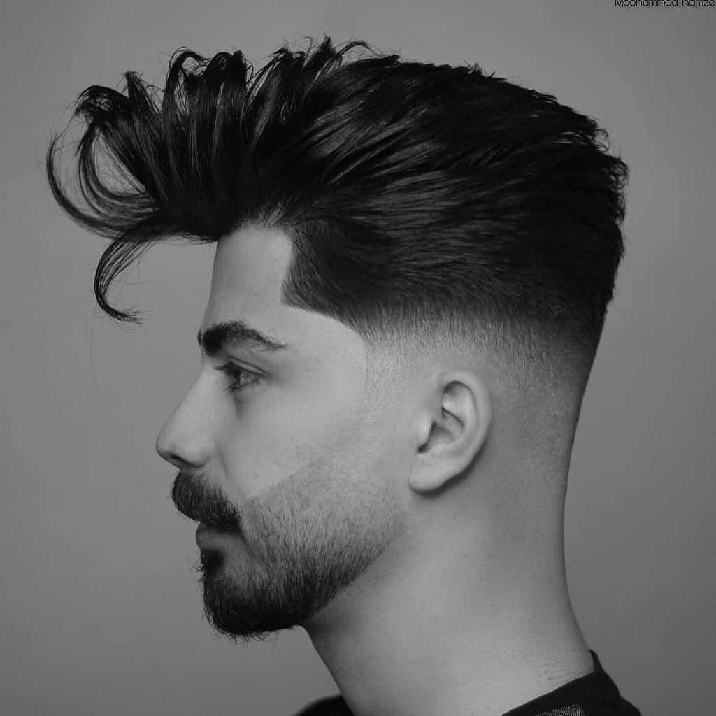 A blown out hair on top paired with mid faded sides and back with clean hairline extending to the beard