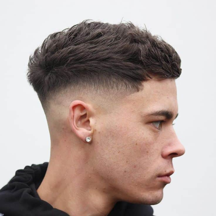 A forward combed quiff paired with a mid-fade
