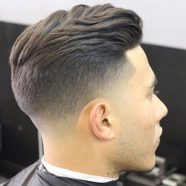 A hairstyle featuring a high fade and tapered sides to reveal the scalp