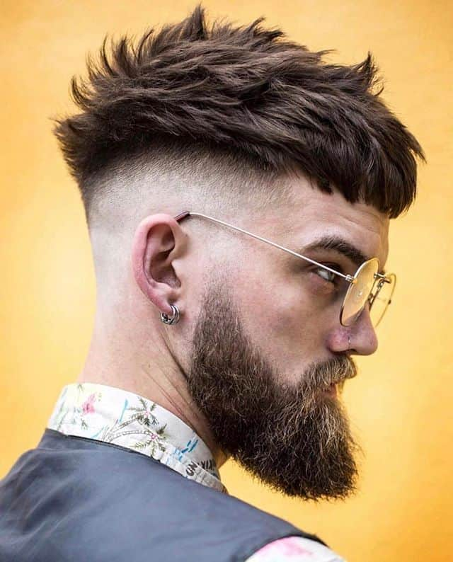 A haircut with thick side swept hair and mid-faded sides and back paired with beard