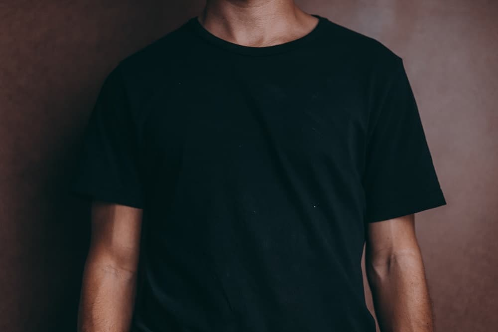 shot of the torso of a model wearing a fitted black t-shirt