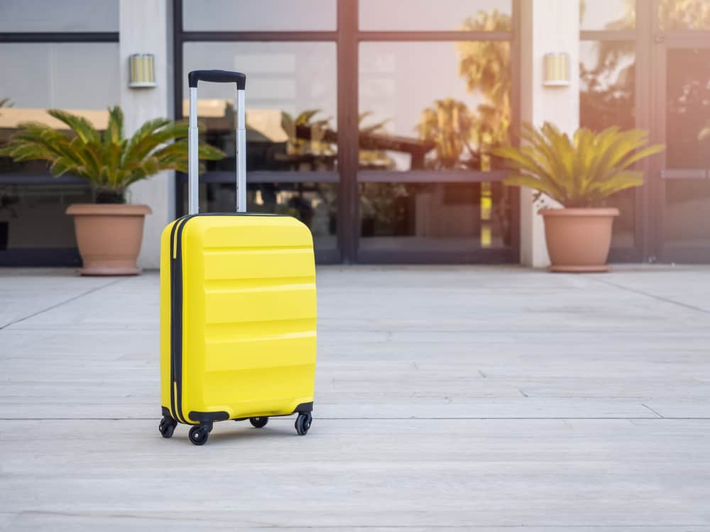 modern yellow cabin suitcase at waiting area in airport