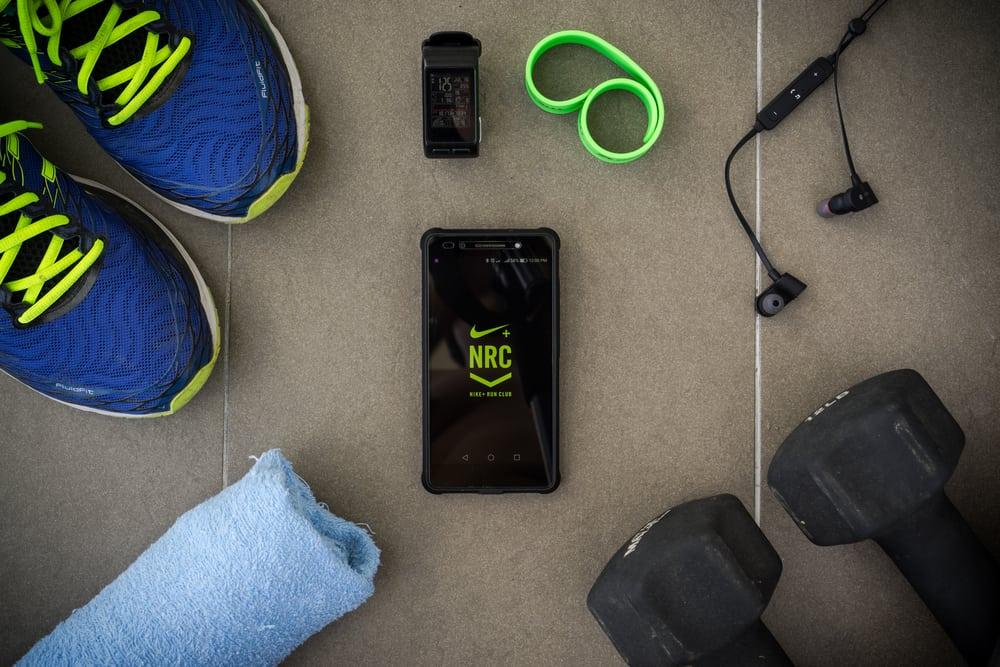 modern lifestyle with smartphone using fitness app nike + run club
