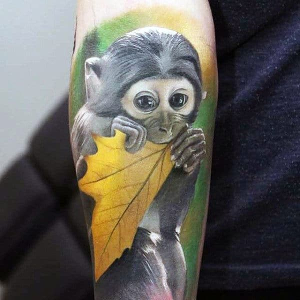 Monkey With Bright Yellow Leaf Mens Tattoo On Inner Forearm