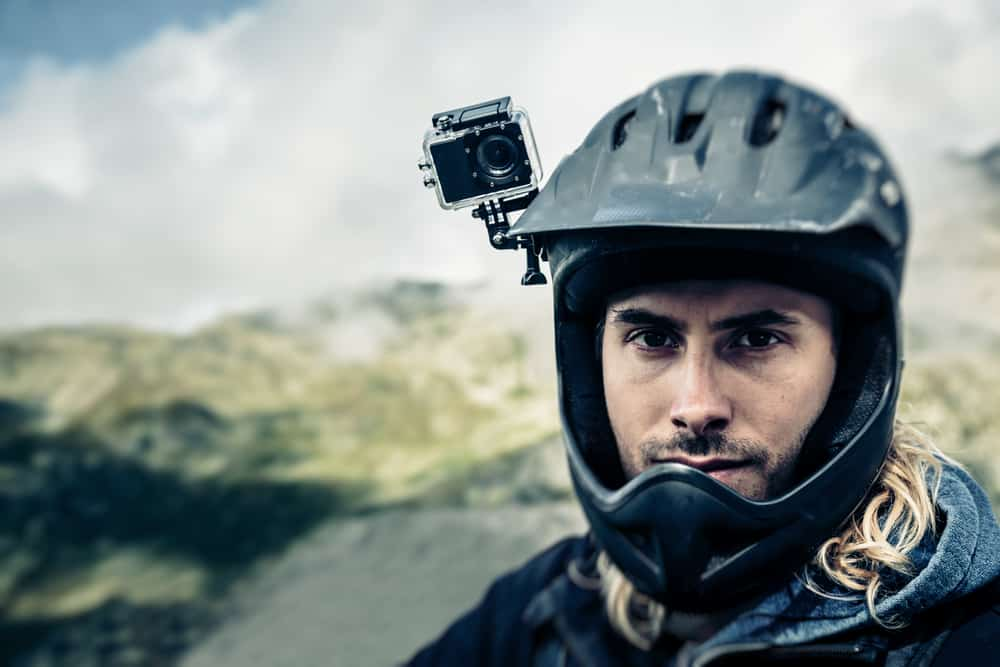 mountain biker with action cam fitted on his black helmet