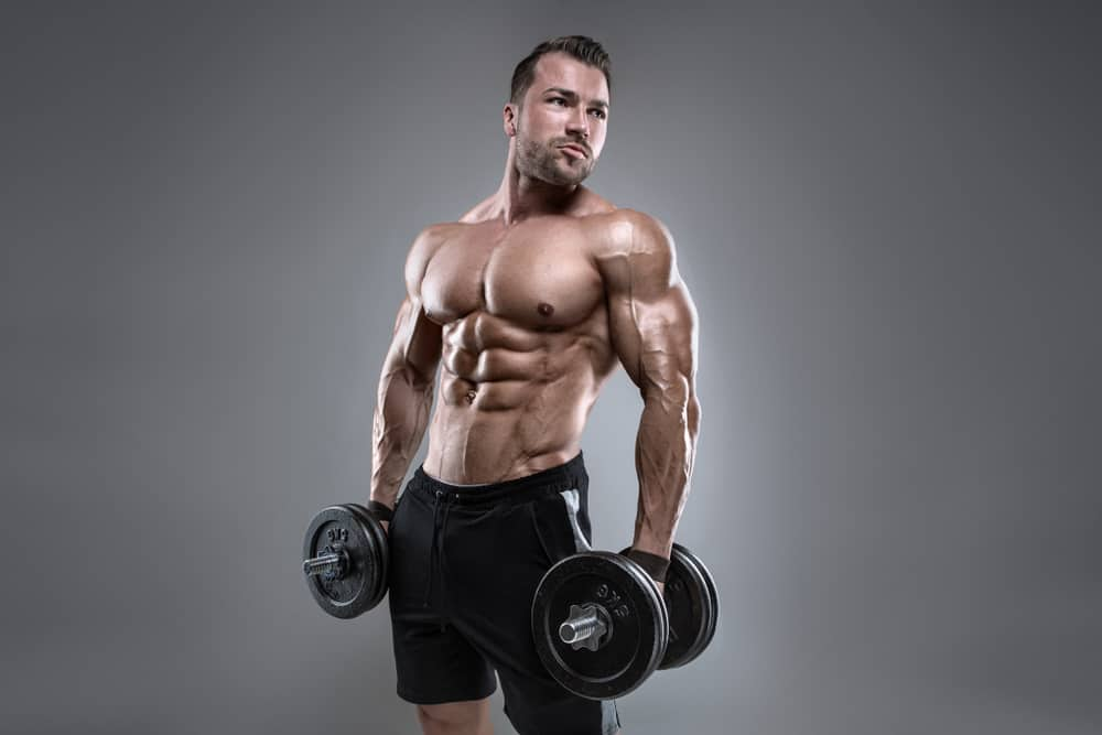muscular bodybuilder guy doing exercise with dumbbell on gray background