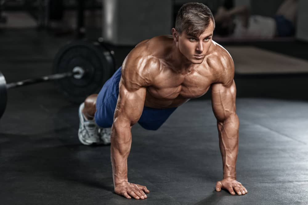 muscular man working out in gym doing push-ups exercise