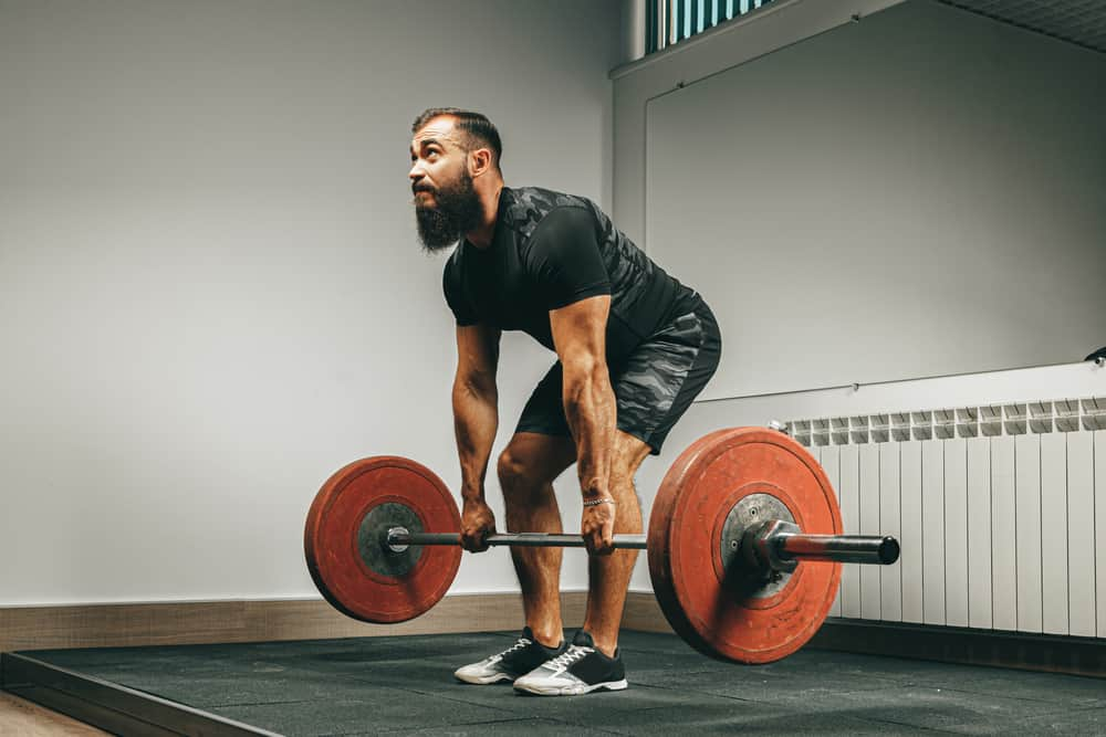 young muscular man in black sportswear lifting barbell in gym