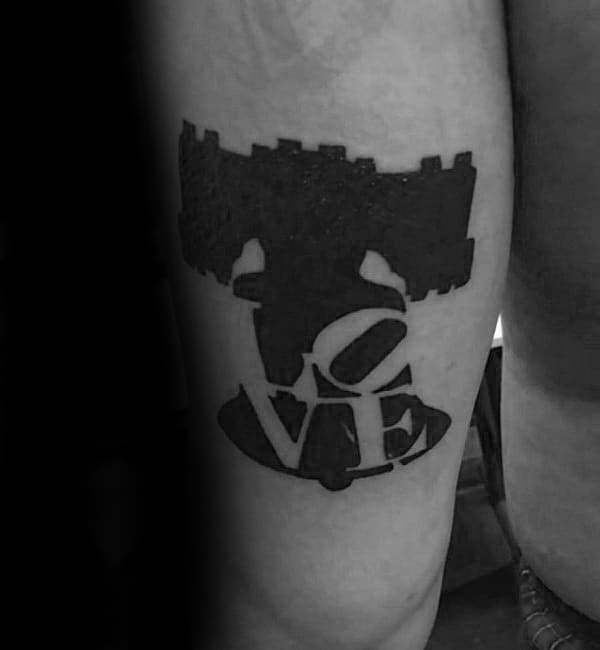 Negative Space Love Liberty Bell Mens Thigh Tattoo With Black Ink Design