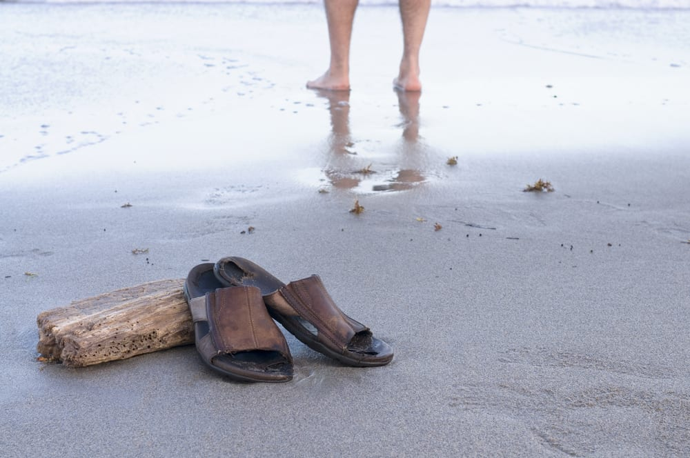 A pair of men's brown slide sandals propped up on driftwood on the beach