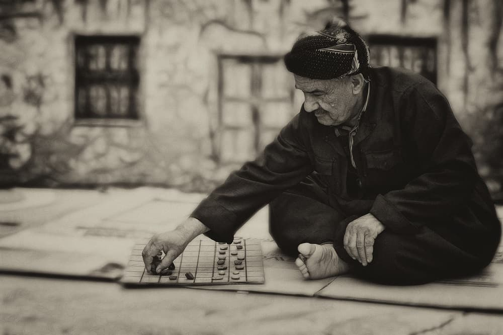 an old man playing board game outdoor