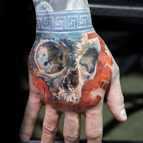Orange With Blue Wrist Band Mens Skull Hand Tattoo Designs