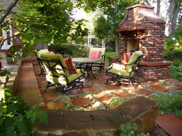 outdoor brick fireplace with green seating
