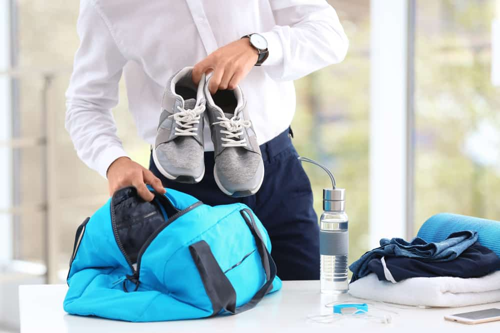 young businessman packing sports stuff into bag for training