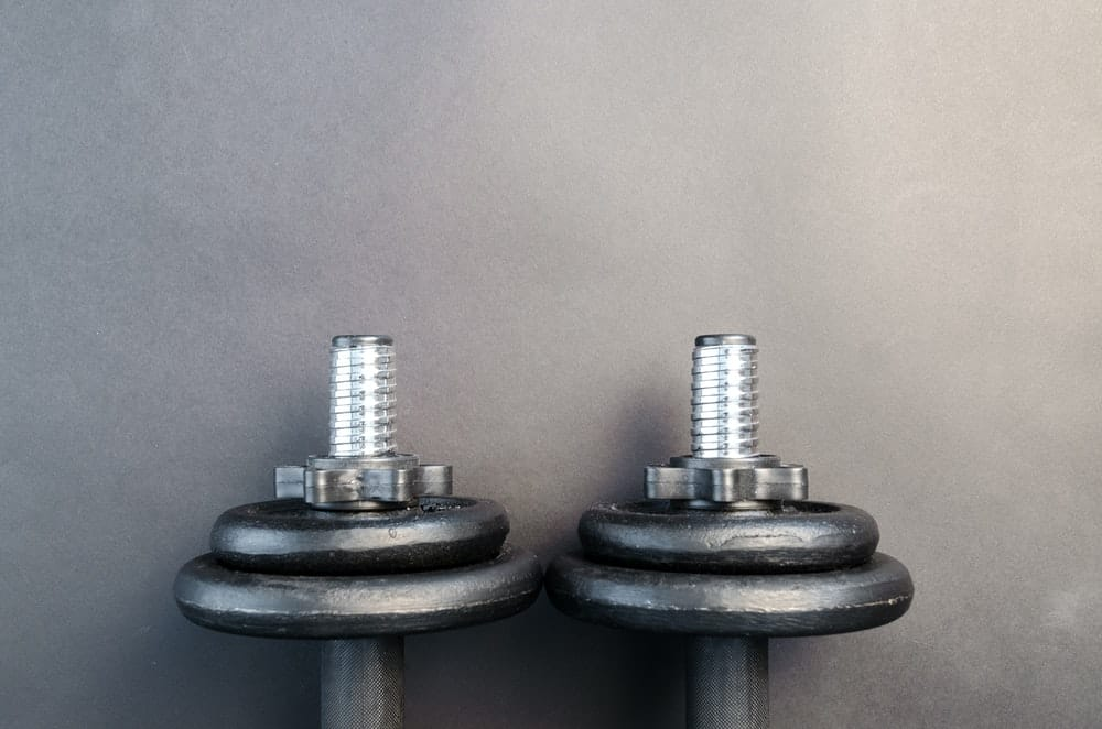 pair of two dumbbells sit on a black surface