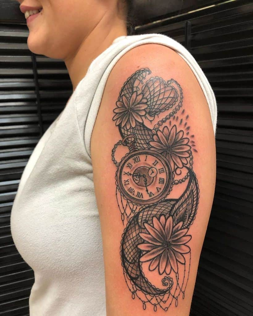 Upper arm tattoo black and grey ornamental paisley pocket watch and daisies