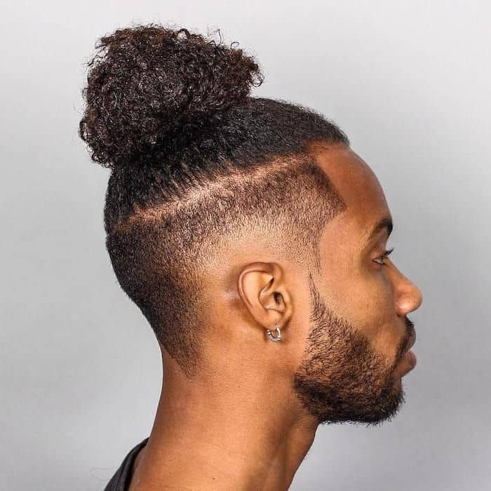 Long hair styled into a ponytail man bun paired with a burst fade