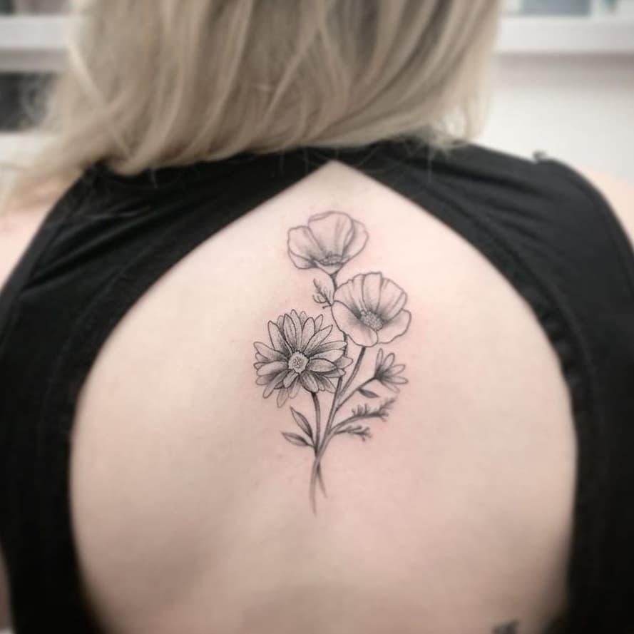 Upper back tattoo black and grey shading poppy daisy bouquet