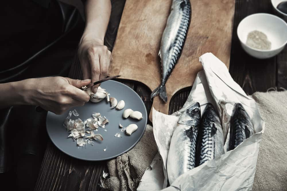 woman preparing mackerel fish for cooking