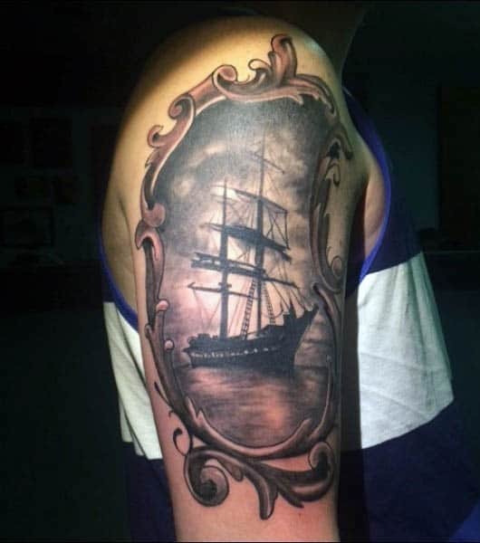 Realistic Framed Sailboat Tattoo On Mans Upper Arm