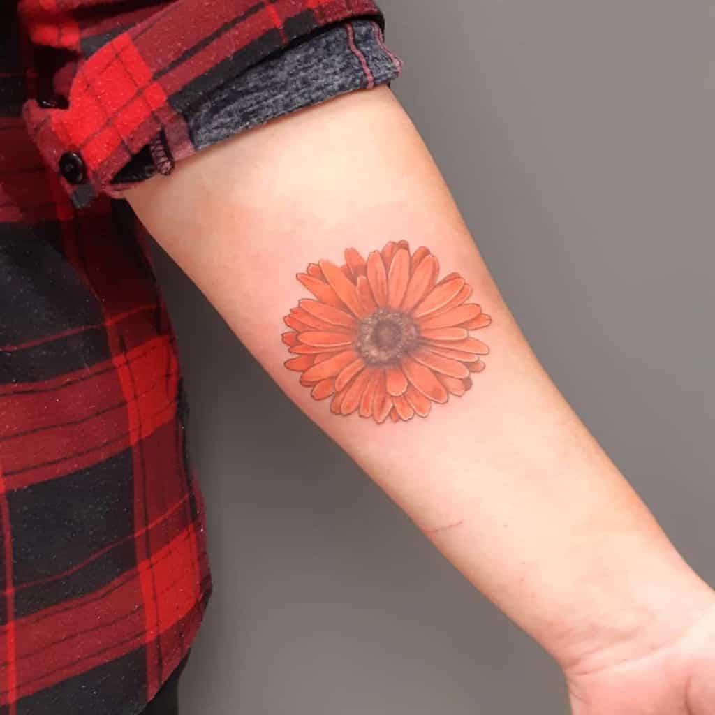 Forearm tattoo realistic orange color daisy