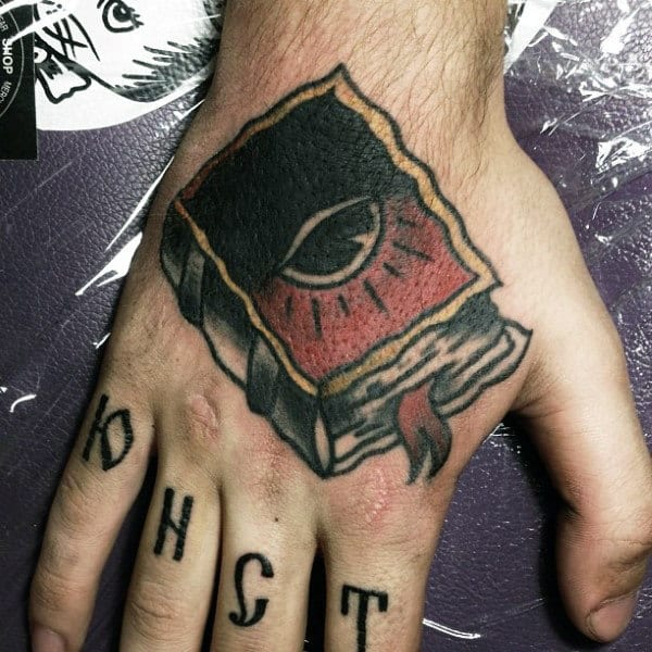 Red And Black One Eyed Book Tattoo Male Hands