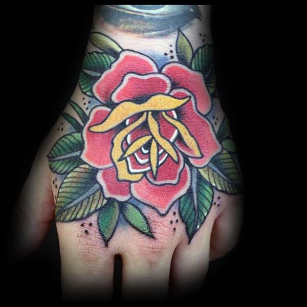 Red And Yellow Traditional Rose Hand Tattoo On Man