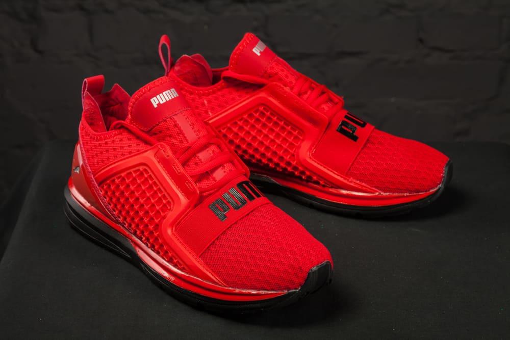 red puma shoes on black surface