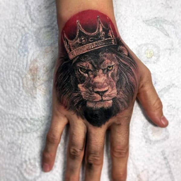red-sun-with-lion-wearing-crown-guys-hand-tattoo