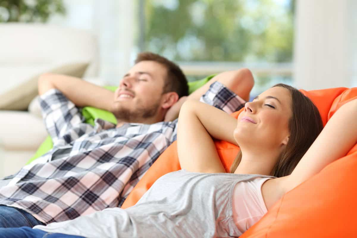 Couple,Or,Roommates,Relaxing,Lying,On,Comfortable,Poufs,In,The