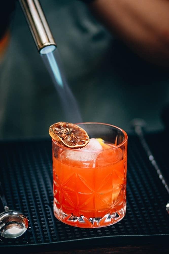 flame into lemon over glass of whiskey