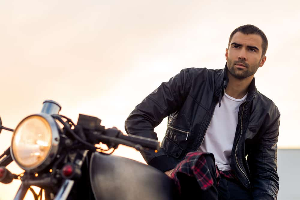 A man wearing a leather jacket and white t-shirt and sitting on a motorcycle